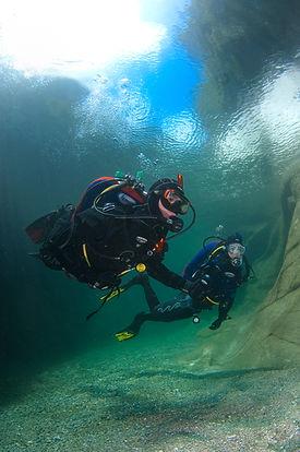 Scuba divers diving near rocks in clear water