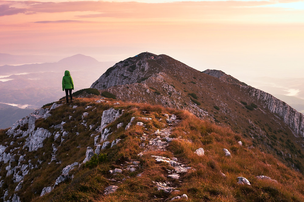 Woman at the top of a mountain at dawn