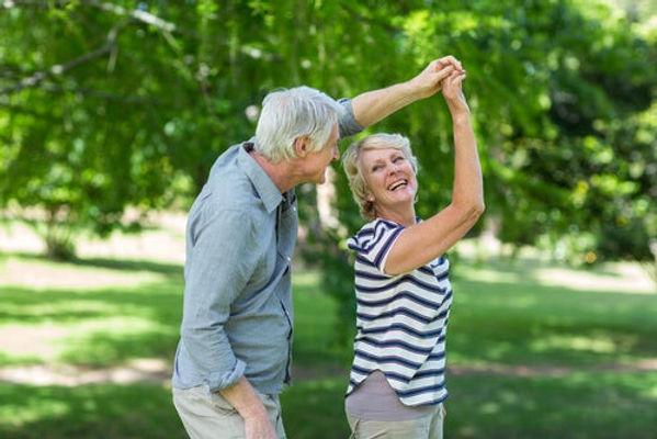 happy older couple dancing outside