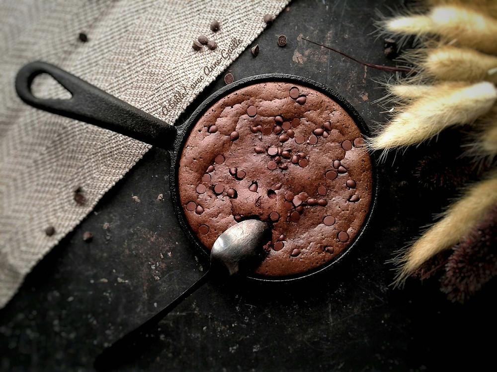 Brownie dans une pœle en fonte sur un plan de travail.