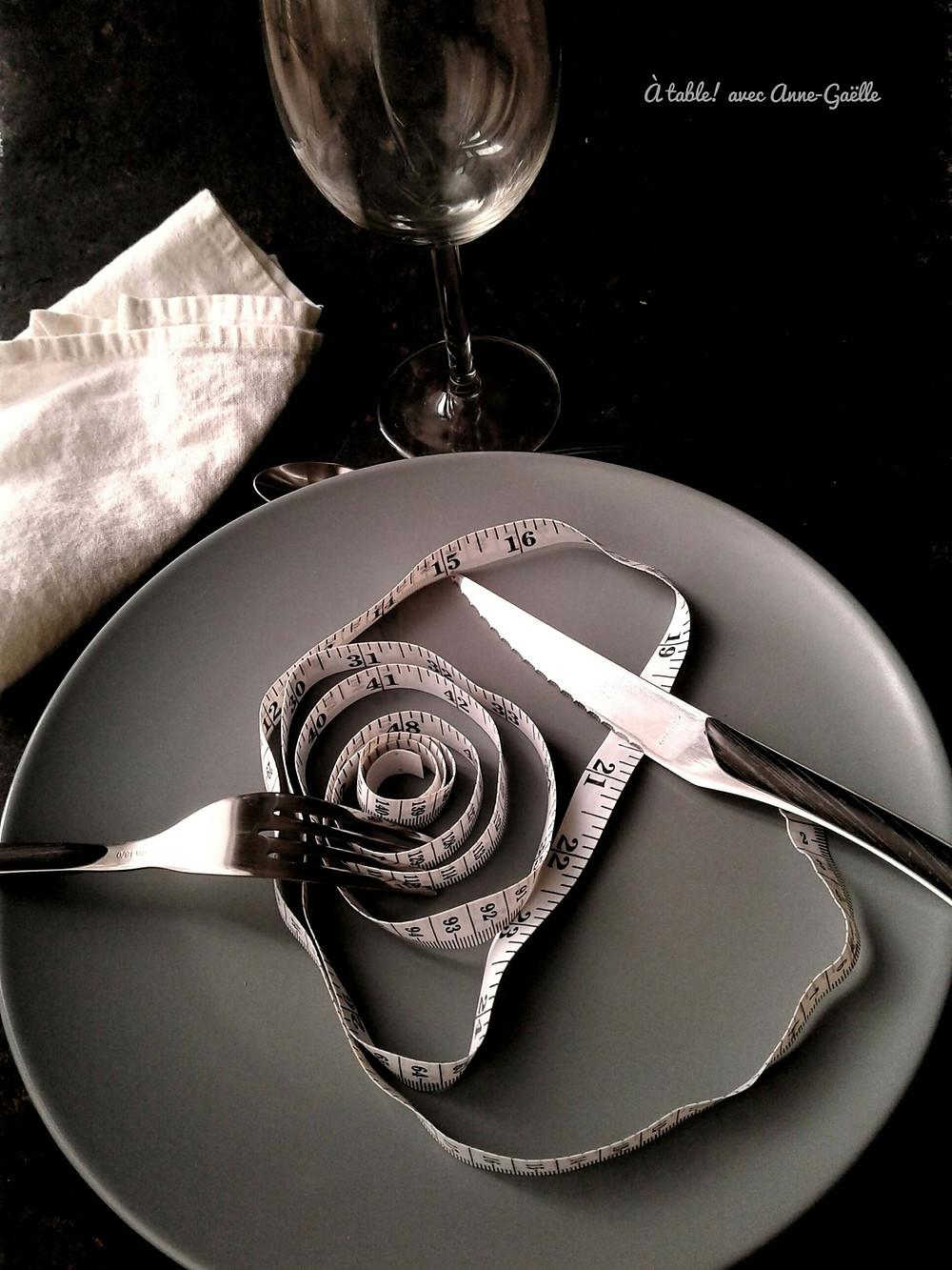 Mètre ruban dans une assiette avec couverts, verre et serviette de table. Symbolisant l'alimentation dans le cadre d'une perte de poid.