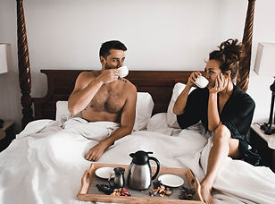 A couple enjoys coffee in bed