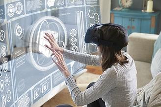 Woman Sits On Sofa At Home Wearing Virtual Reality Headset.jpg