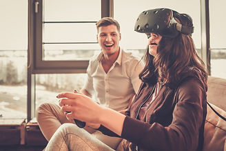 Cheerful couple having fun with VR in home interior.jpg