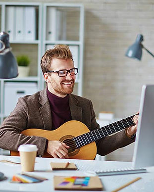 man-playing-guitar-computer-lessons-onli