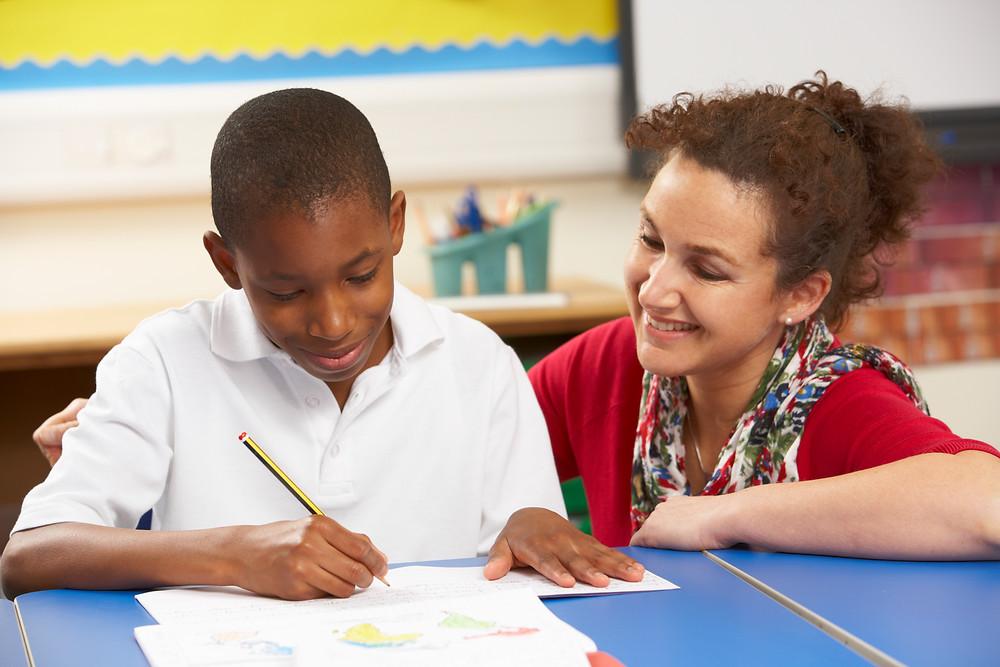 Professora junto com um alunos fazendo uma atividade escolar. Os dois olham para a mesa sorrindo ao fundo há alguns materiais escolares.