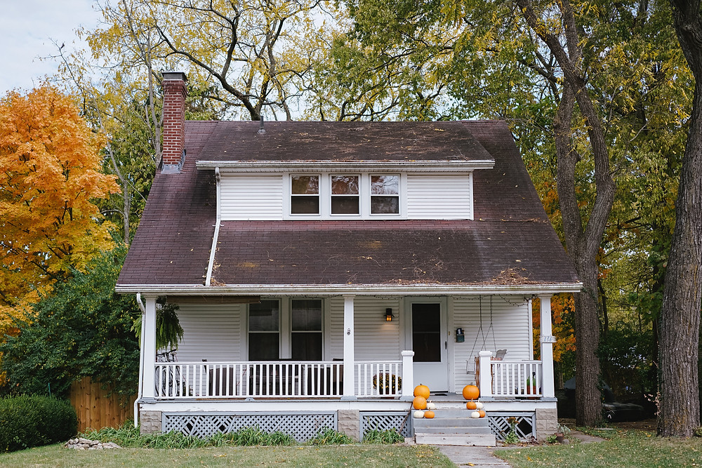 Casa branca com chaminé e varanda, rodeada por árvores e feita de madeira. Tem um balanço e cadeiras na sua varanda, além de arranjos laranjas nos cantos da pequena escada de entrada.