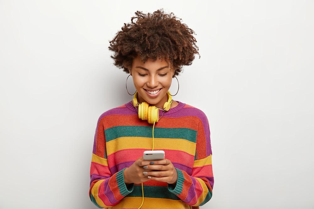 Menina com blusa colorida mexendo no celular. Ela tem um fone amarelo enrolado no pescoço e usa brincos argolas. O fundo da imagem é beje.