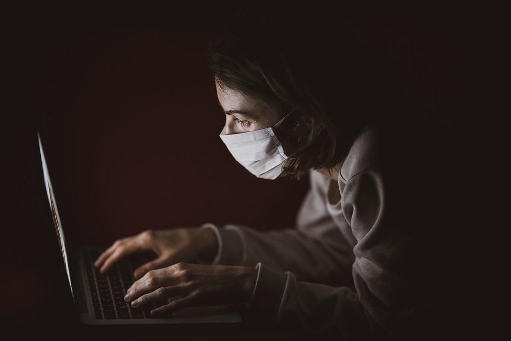 Mulher escrevendo no computador em um ambiente escuro e usando uma mascara, simbolizando as questões de proteção contra a pandemia.