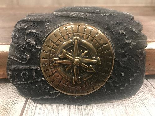 Brass compass on black lava base