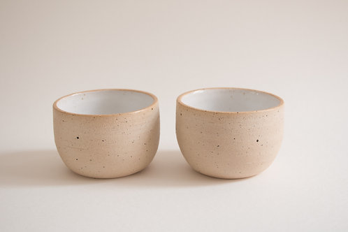 rounded white flecked coffee cups