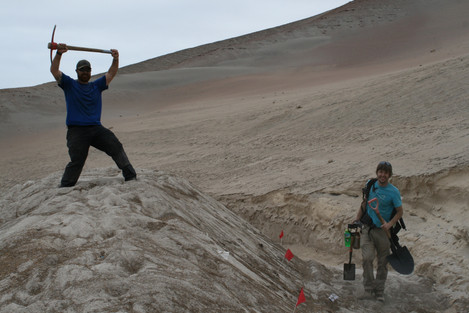 Mike Cook and Taylor Panczak dig to uncover a road blocked by migrating dunes. Photograph by Emily Milton