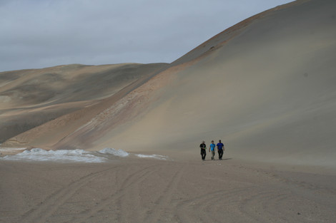 Kurt Rademaker, Taylor Panczak, and Mike Cook survey in front of a dune. Photograph by Emily Milton