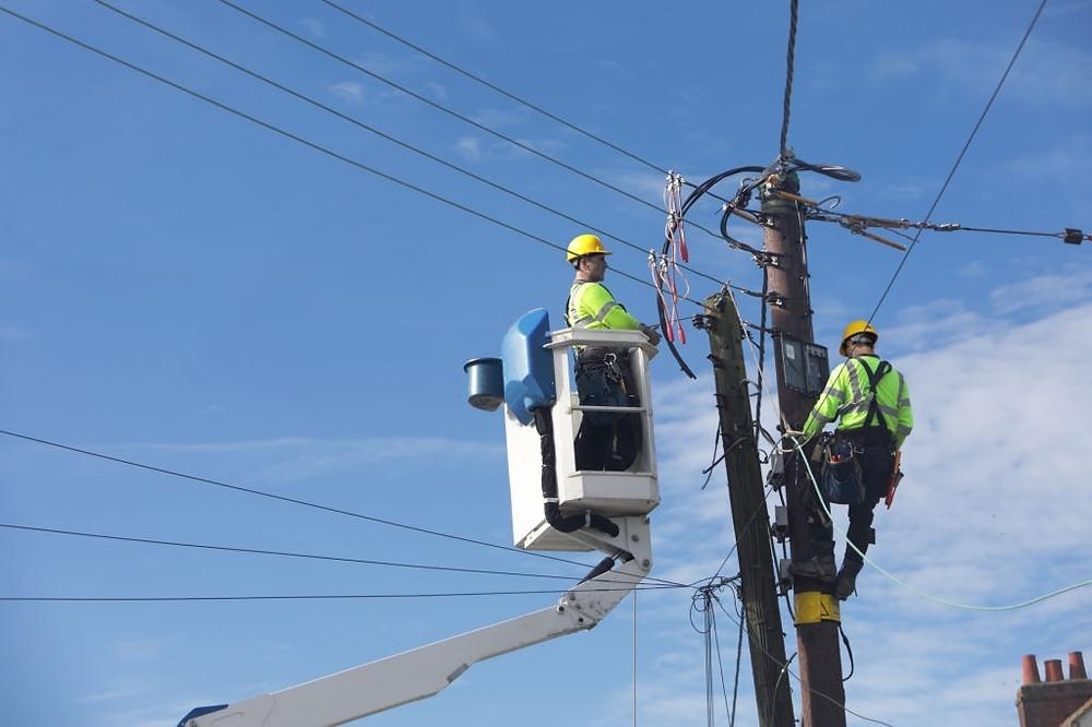 dos operarios de la electricidad subidos a una plataforma elevadora arreglando la electricidad