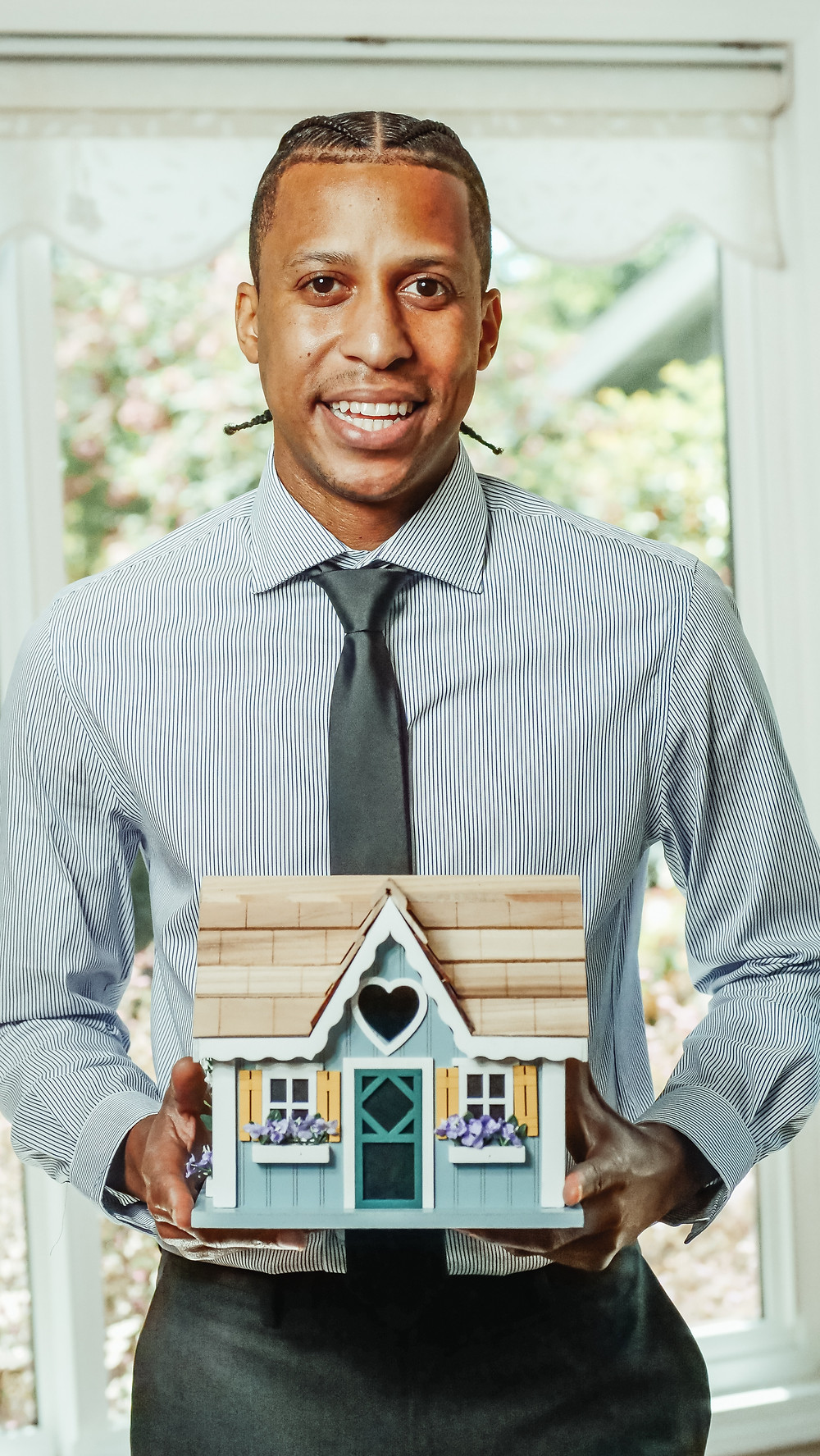 a black man in a striped shirt with dark grey tie smiling and holding a house model in front of him