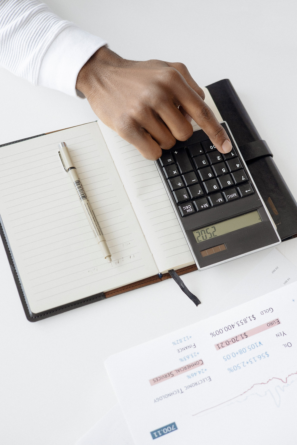 black woman's hand using a calculator on top of a notebook under a financial statement