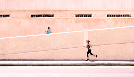 A man running up a ramp, and woman running below on flat ground.