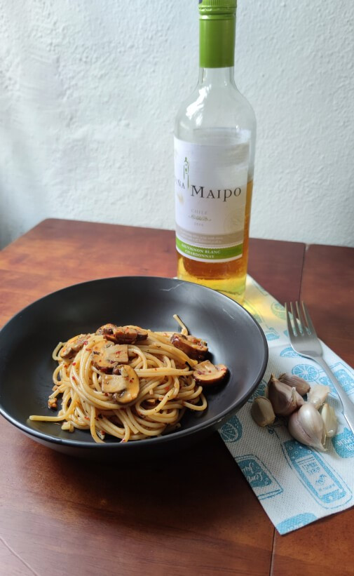 A bowl of garlic mushroom spaghetti, with a bottle of white wine and a fork nearby