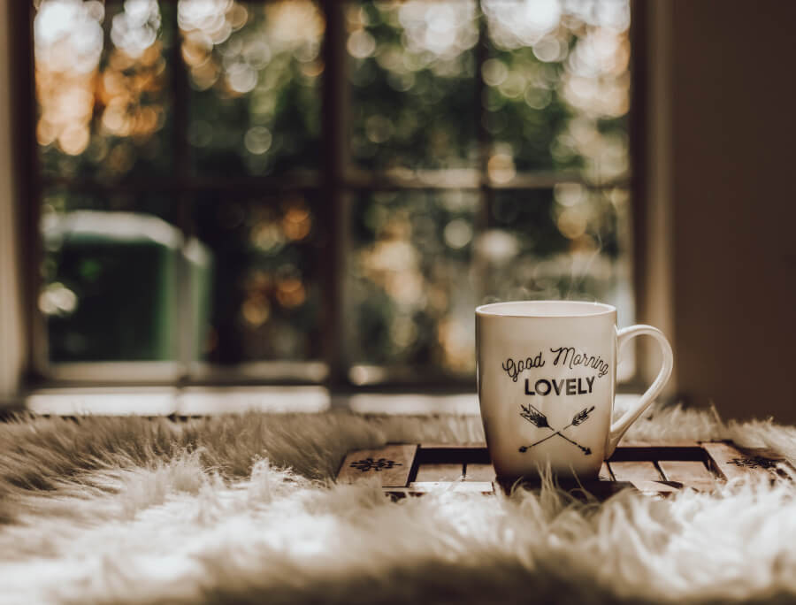 A coffee mug with the words 'Good Morning Lovely' next to a window overlooking some trees