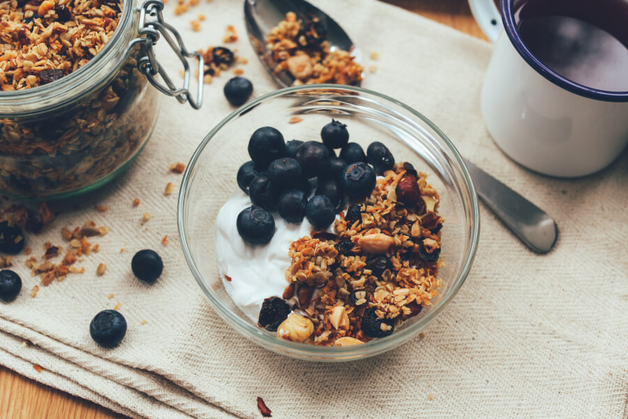 A bowl of yogurt, blueberries, and homemade granola with a spoon nearby