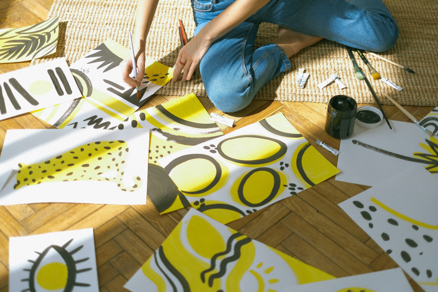 A woman painting using two colours, namely yellow and black