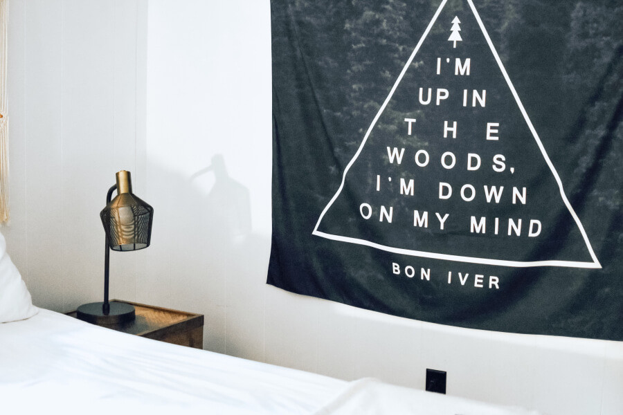 A black tapestry on the wall next to a bed and bedside table