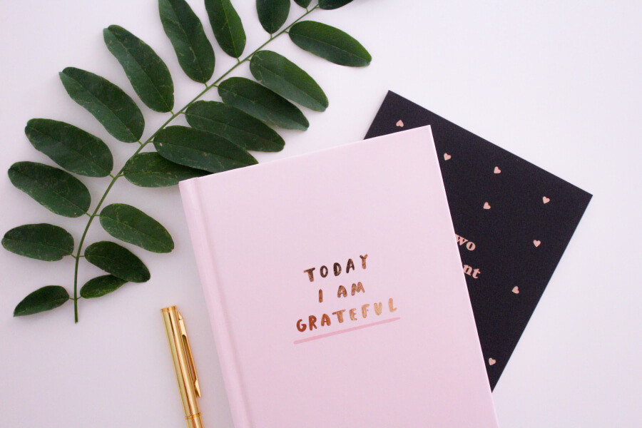 A pink journal with the words 'Today I Am Grateful' on it, with a gold pen nearby