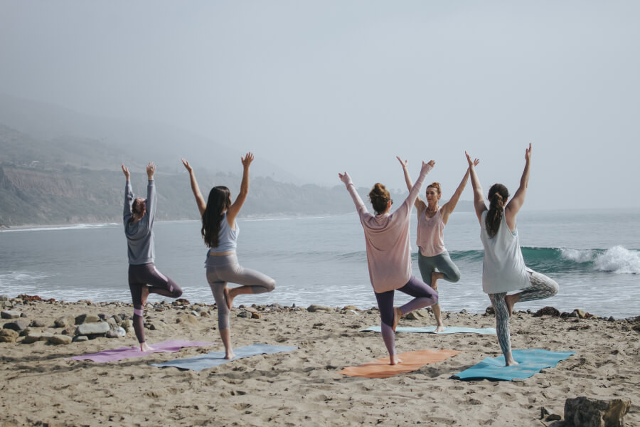 A group of women doing yoga together on a beach