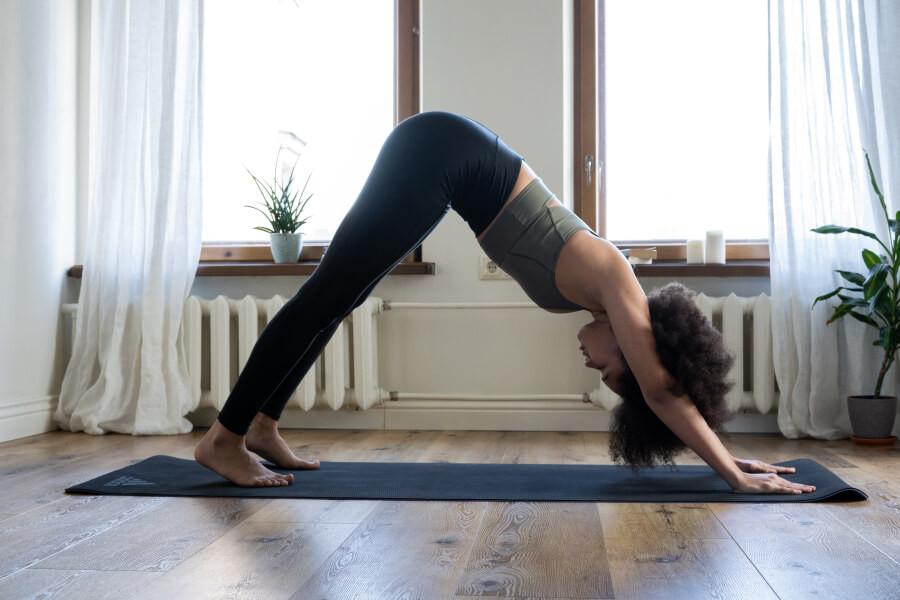 A woman doing the downward-facing dog yoga pose on a yoga mat