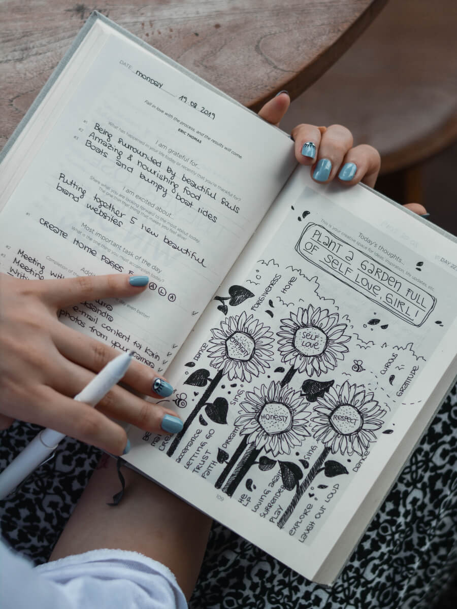 A woman doodling some flowers in her journal