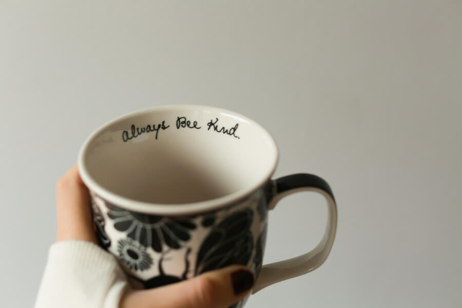 A woman holding a mug with the words 'Always bee kind'