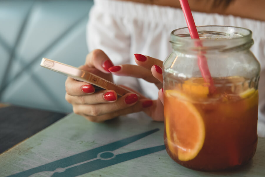 A woman using a smartphone with a glass of iced tea nearby