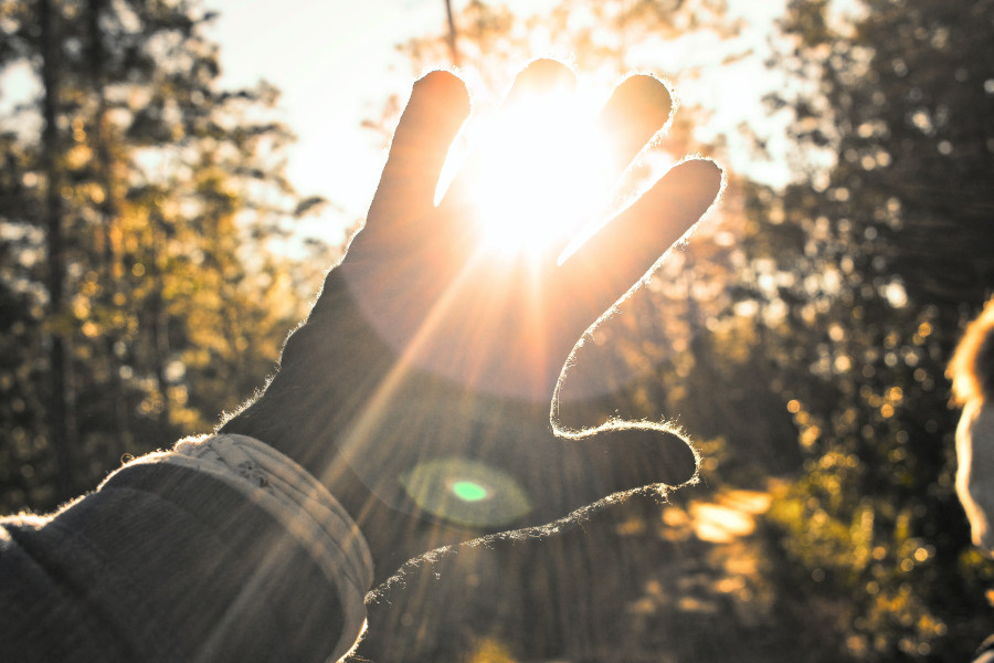 A person holding up their hand to shield themselves from the sun