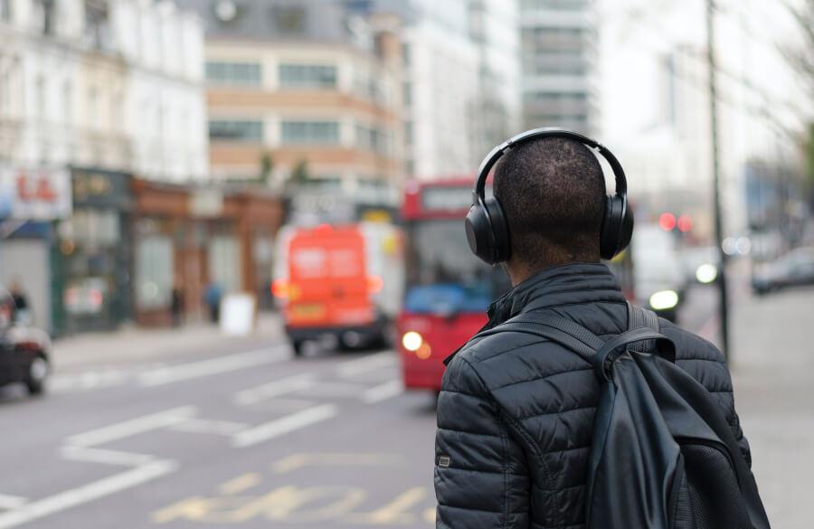Man wearing headphones crossing the street