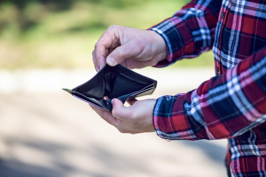 A man in a checkered shirt holding an empty wallet