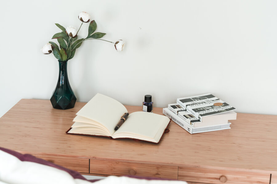 An open journal and a fountain pen on a desk, with books and a vase of flowers nearby