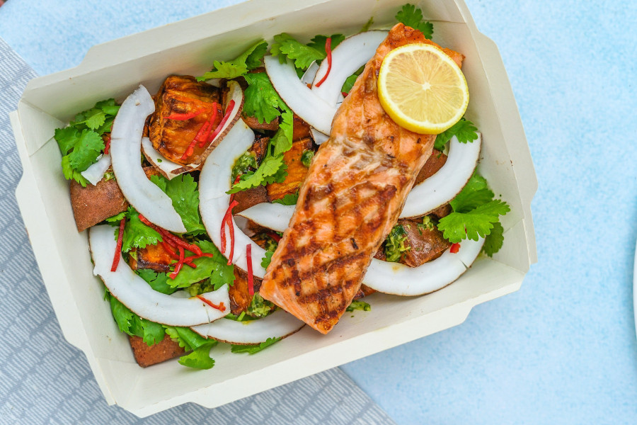 A container filled with vegetables, salmon, and lemon slices