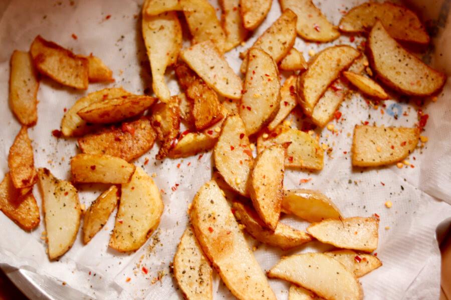 Crispy potato wedges on a baking tray