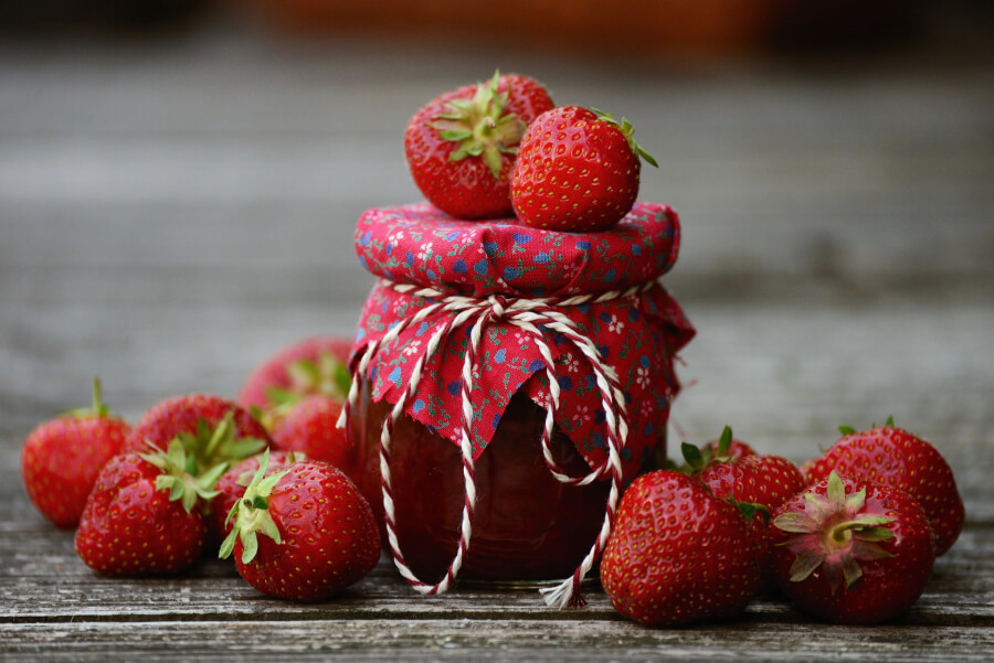 A jar of homemade strawberry jam with fresh strawberries nearby
