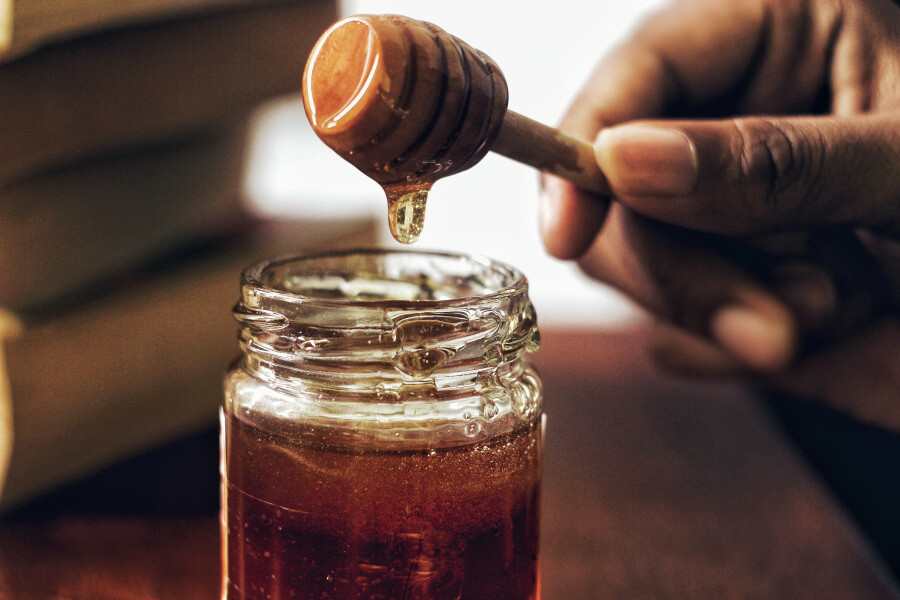 A person dipping a honeycomb stick into a jar of honey