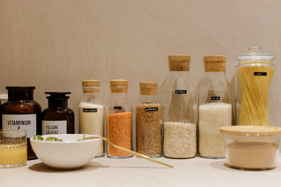 Glass jars with oatmeal, lentils, rice, and spaghetti on a kitchen countertop