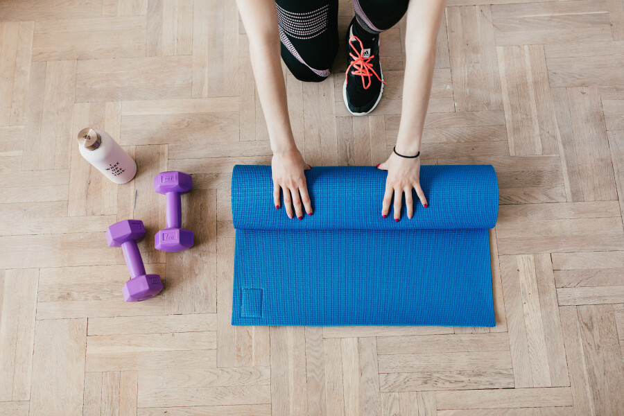 A woman wearing sports shoes unrolling a yoga mat, with weights and a water bottle nearby.