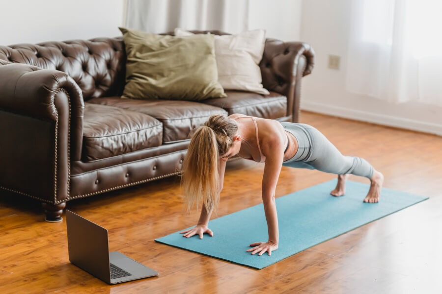 A woman doing yoga on a yoga mat with a laptop in front of her