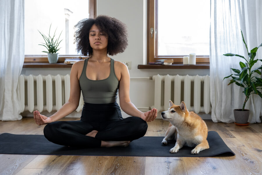 Woman meditating on the floor with a dog beside her