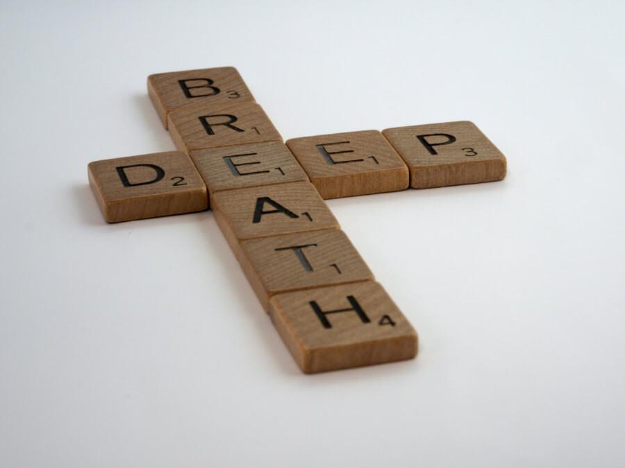 Scrabble pieces arranged to spell 'deep breath'