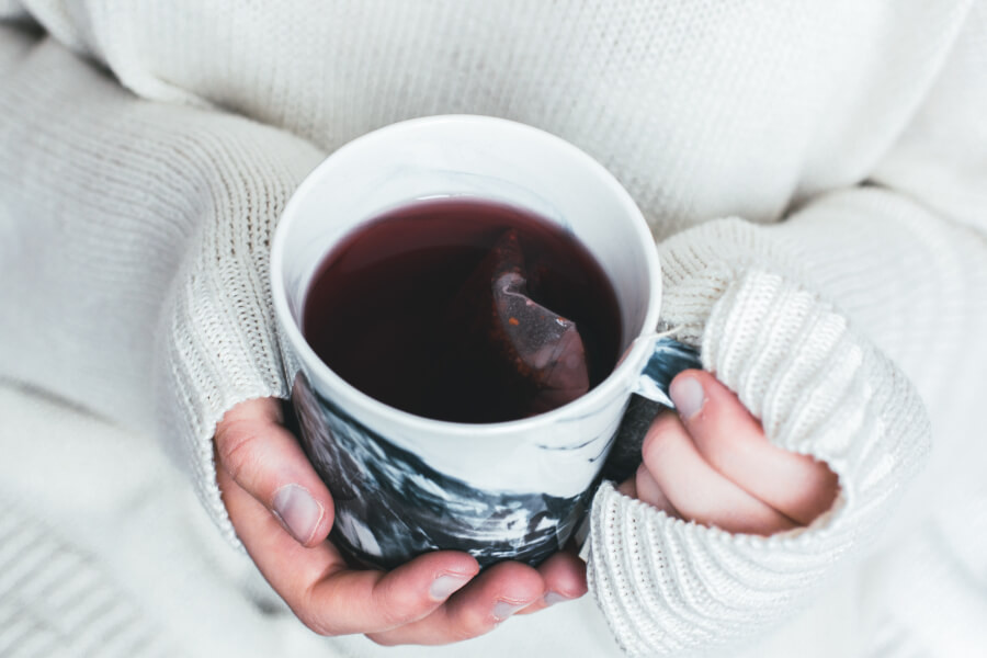A woman holding a hot cup of tea