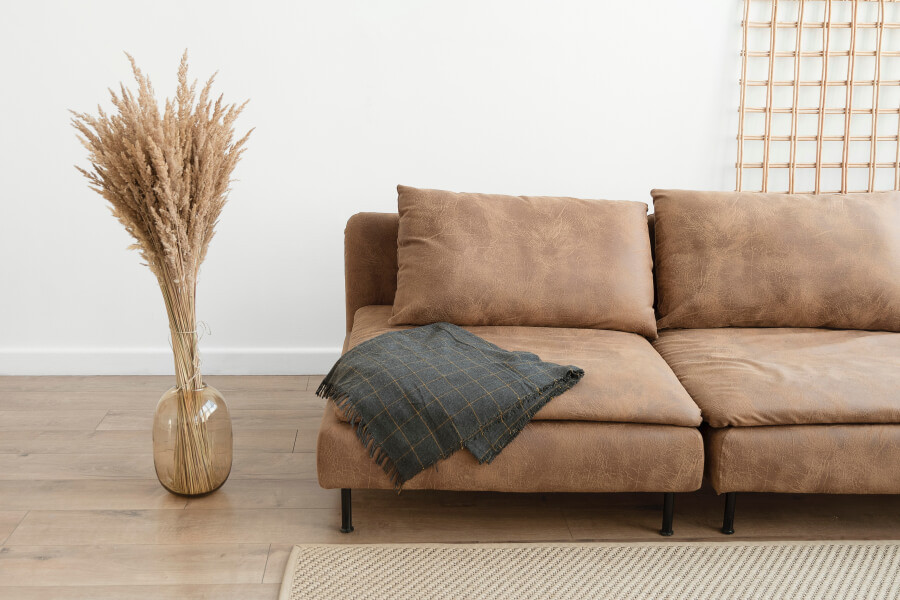 A vase of dried pampas grass next to a couch