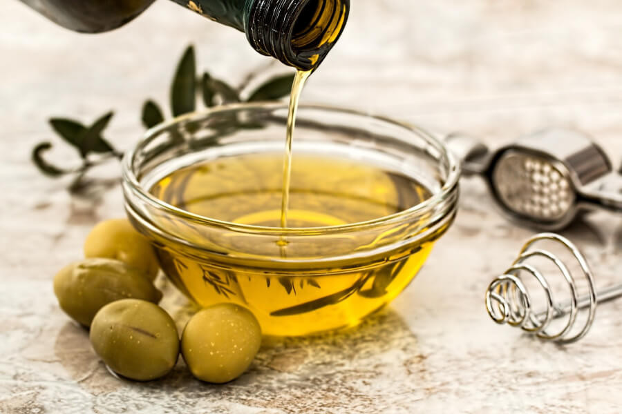 A person pouring extra virgin olive oil from a bottle into a small bowl