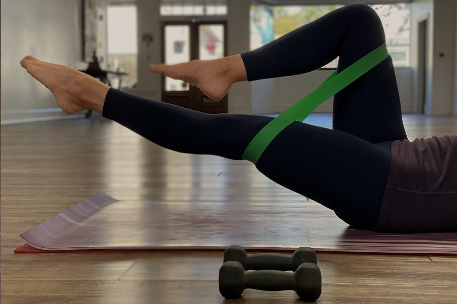 A woman exercising with a resistance band and weights