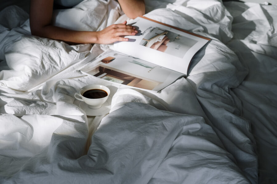 A woman flipping through a magazine in bed with a cup of black coffee nearby